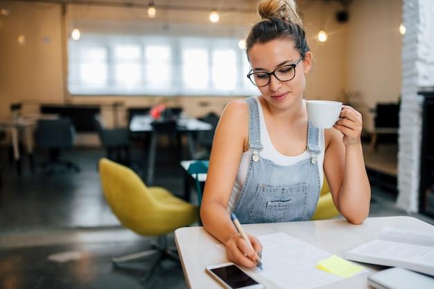 Junge kluge studentin, die hausarbeit tut und sich für prüfung im college vorbereitet.