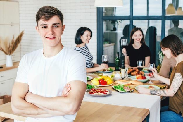 Junge kochen in einem fest mit leuten in der küche in einer wohnung