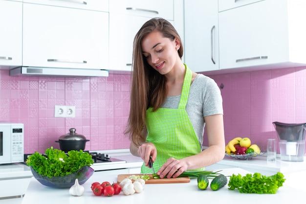 Junge kochende frau, die gemüse für gesunde frische salate und geschirr in der küche zu hause hackt