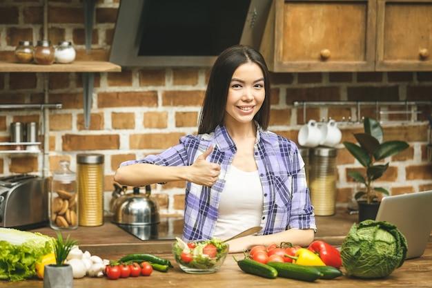 Junge kochende frau, die in der nähe des schreibtischs lächelnd steht und kamera betrachtet, zeigt daumen hoch