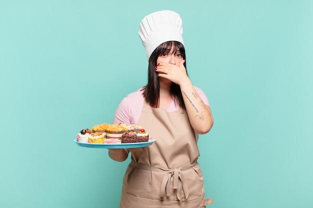 Junge kochfrau, die den mund mit den händen mit einem schockierten, überraschten ausdruck bedeckt, ein geheimnis hält oder oops sagt