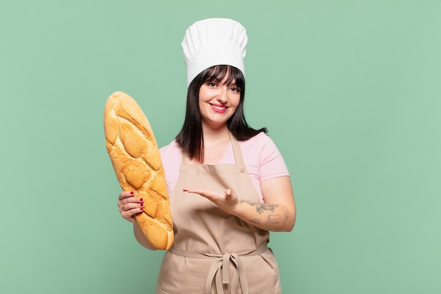 Junge kochfrau, die fröhlich lächelt, sich glücklich fühlt und ein konzept im kopierraum mit der handfläche zeigt