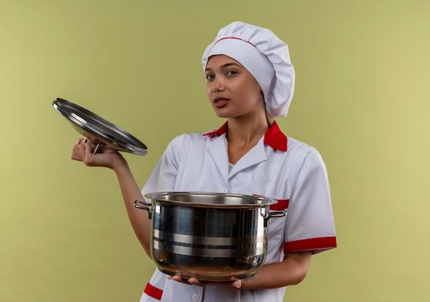 Junge kochfrau, die kochuniform trägt, die topf und deckel auf isolierter grüner wand hält