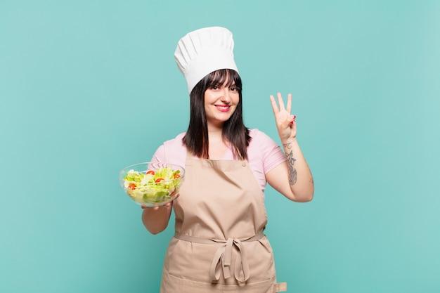 Junge kochfrau, die lächelt und freundlich aussieht, nummer drei oder dritte mit der hand nach vorne zeigt, herunterzählt