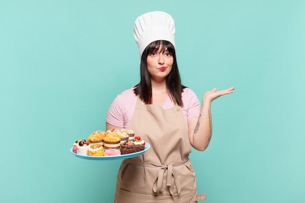 Junge kochfrau, die sich verwirrt und verwirrt fühlt, zweifelt, gewichtet oder verschiedene optionen mit lustigem ausdruck wählt