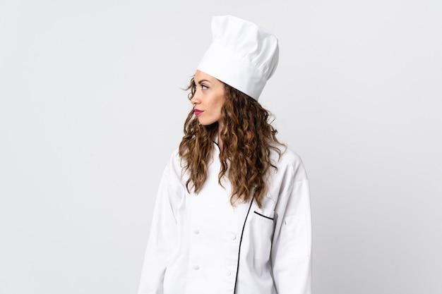 Junge kochfrau lokalisiert auf weiß, das zur seite schaut