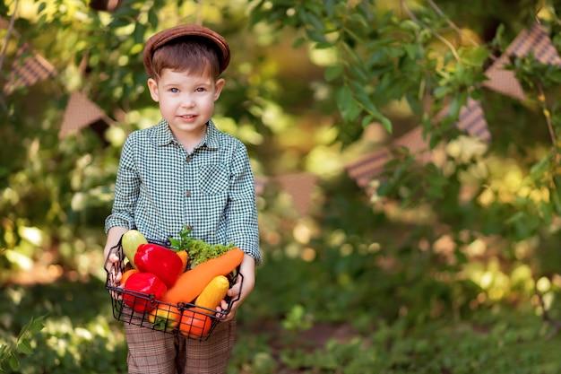 Junge kocht einen gemüsesalat in der natur. gärtner sammelt eine ernte von gemüse. lieferung von produkten
