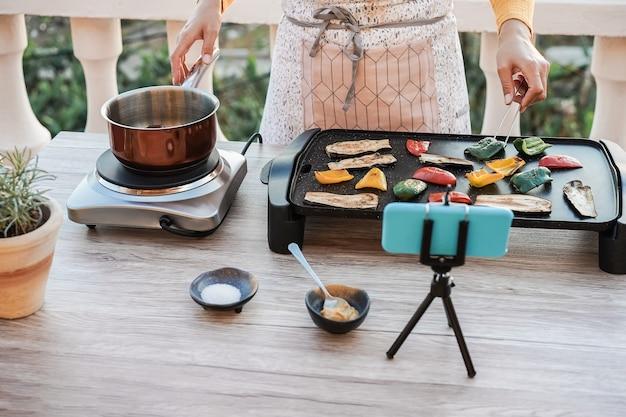 Junge köchin, die draußen kocht, während sie online für webinarunterricht zu hause streamen - hauptfokus auf gemüse