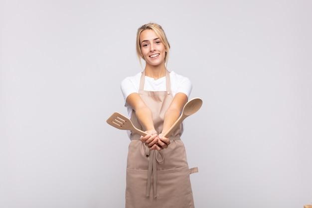 Junge köchin, die glücklich mit freundlichem, selbstbewusstem, positivem blick lächelt, ein objekt anbietet und zeigt