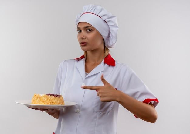 Junge köchin, die kochuniform trägt, zeigt finger auf kuchen auf teller in ihrer hand auf isolierter weißer wand mit kopienraum