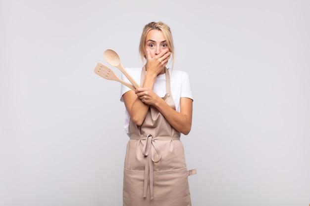 Junge köchin, die mund mit den händen mit einem schockierten, überraschten ausdruck bedeckt, ein geheimnis hält oder oops sagt