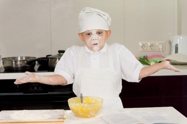 Junge köchin mit einem gesicht voller mehl zuckend