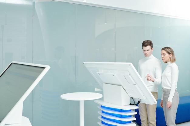 Junge kollegen des informationszentrums verwenden ein großes interaktives display, während sie gemeinsam daten im büro analysieren