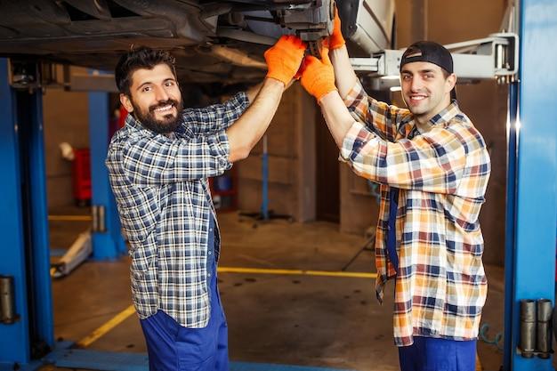 Junge kollegen, die bei der reparatur von autoreifen im servicecenter in die kamera schauen
