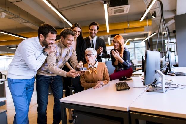 Junge kollegen feiern im büro den geburtstag eines älteren kollegen und bringen einen kuchen mit