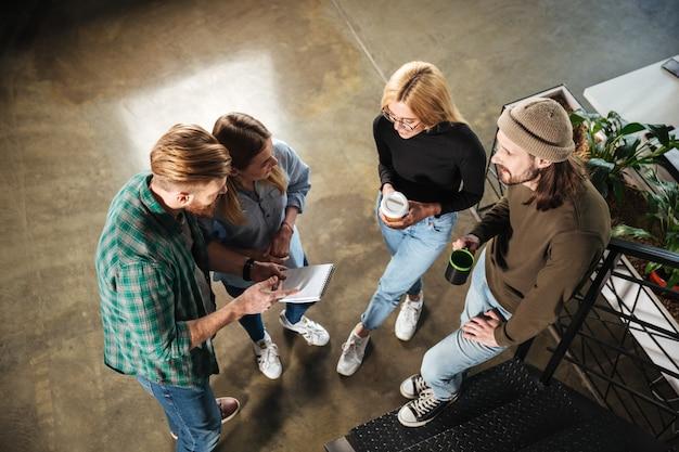 Junge kollegen im büro, die miteinander sprechen und notizbuch halten