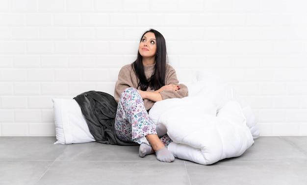 Junge kolumbianische frau in den pyjamas zuhause beim lächeln oben schauen