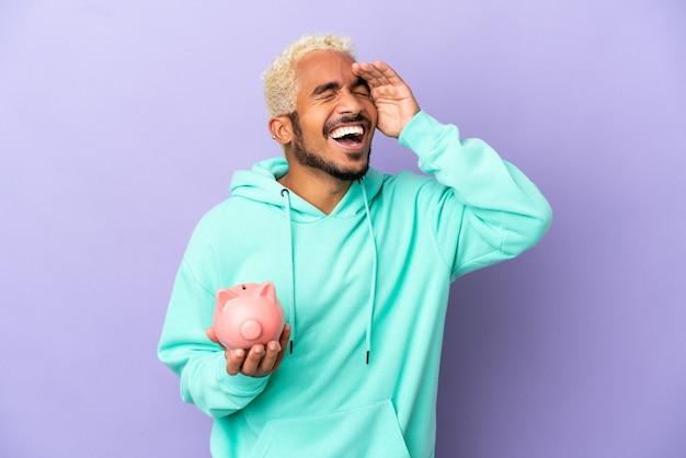 Junge kolumbianische mann hält ein sparschwein isoliert auf lila hintergrund lächelnd viel