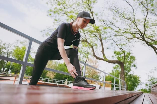 Junge konzentrierte athletische brünette frau in schwarzer uniform, mütze mit kopfhörern, die musik hören und sport strecken, übungen zum aufwärmen auf der bank im stadtpark im freien