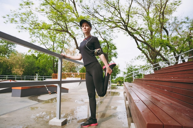 Junge konzentrierte athletische schöne brünette frau in schwarzer uniform, mütze mit kopfhörern, die musik hören und sport strecken, übungen zum aufwärmen im stadtpark im freien