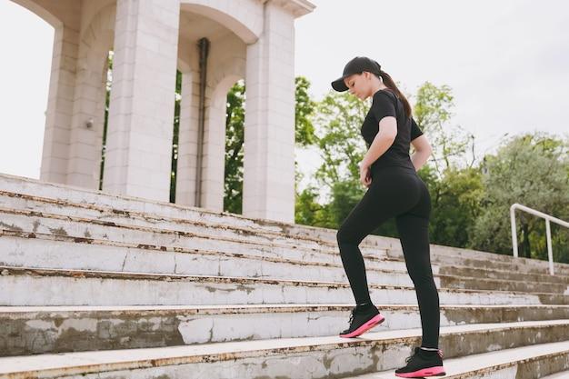 Junge konzentrierte athletische schöne brünette frau in schwarzer uniform und mütze macht sportübungen, aufwärmen vor dem laufen auf treppen im stadtpark im freien klettern