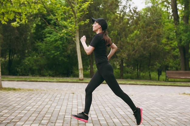 Junge konzentrierte athletische schöne frau in schwarzer uniform und mütze training macht sportübungen laufen, joggen, blick direkt auf den weg im stadtpark im freien