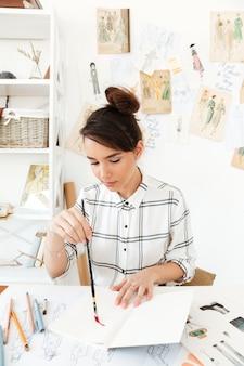 Junge konzentrierte frau modeillustrator