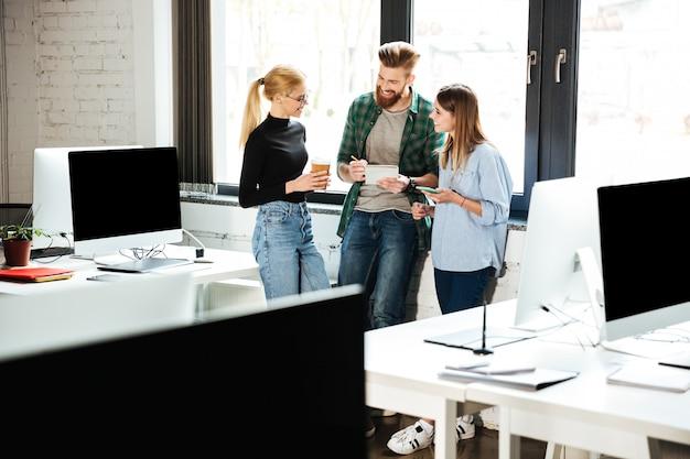 Junge konzentrierte kollegen im büro sprechen miteinander