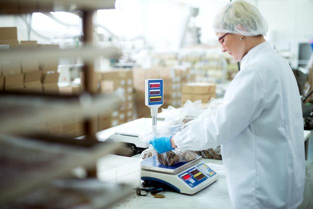 Junge konzentrierte müde arbeiterin in sterilen tüchern, die gesunde nahrungsmittelsnacks messen, bevor sie verpackt werden.