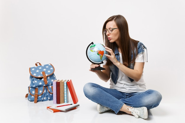 Junge konzentrierte studentin, die die weltkugel hält und die über länder sucht, die in der nähe des rucksacks sitzen, schulbücher isoliert