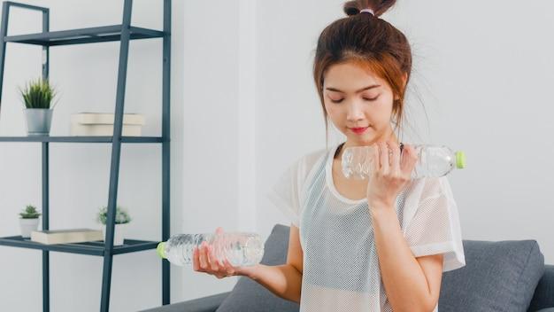 Junge koreanische dame in sportbekleidungsübungen, die unter verwendung der leichten hantel mit der flasche wasser auf der couch im wohnzimmer zu hause trainieren