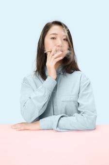 Junge koreanische frauen, die zigarre rauchen, während am tisch im studio sitzen.