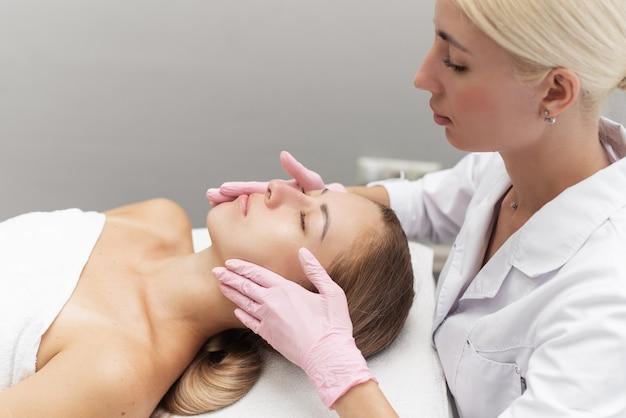 Junge kosmetikerin oder dermatologe, die manuelle gesichtsreinigung für eine frau in einem schönheitssalon durchführt