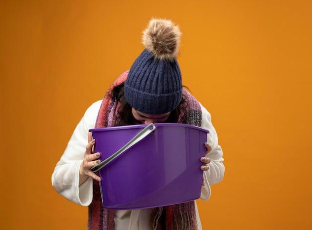 Junge kranke frau, die robe wintermütze und schal trägt, die übelkeit hält, die plastikeimer erbricht, der in sie auf orange wand lokalisiert erbricht