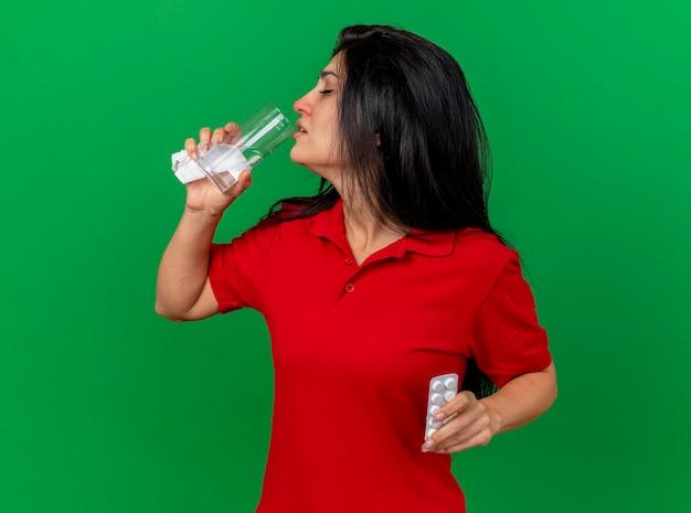 Junge kranke frau, die serviettenpackung der tabletten trinkt, trinkt wasser vom glas mit geschlossenen augen lokalisiert auf grüner wand mit kopienraum
