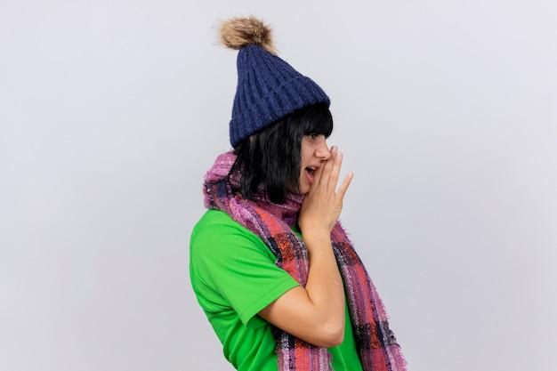 Junge kranke frau, die wintermütze und schal trägt, die in der profilansicht stehen und gerade hand in der nähe des mundes halten flüstern lokalisiert auf weißer wand suchen