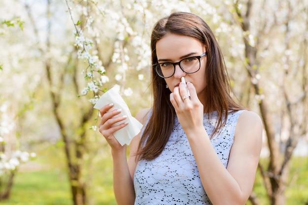 Junge kranke frau mit fieber oder allergie in der frühlingsblüte hält inhalator und weiße serviette im park im frühjahr