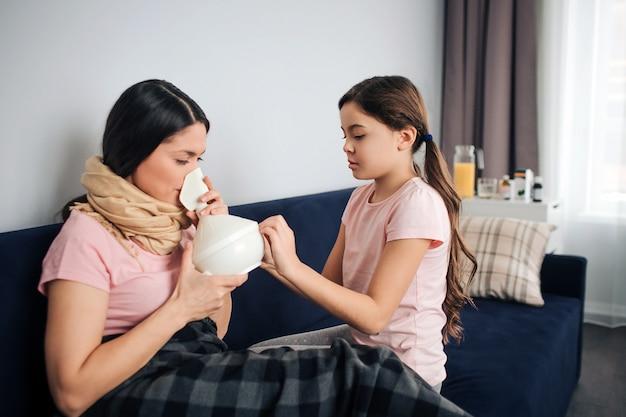 Junge kranke frau sitzen auf couch mit ihrer tochter im zimmer. sie atmet medizin durch inhalator ein. brünette halte es. kind sitzt neben und hilft ihrer mutter.