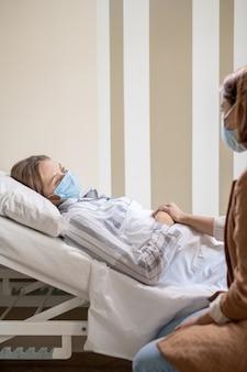 Junge kranke patientin im schlafanzug und schutzmaske, die im bett in der krankenhauskammer liegt und ihre freundin während des gesprächs ansieht