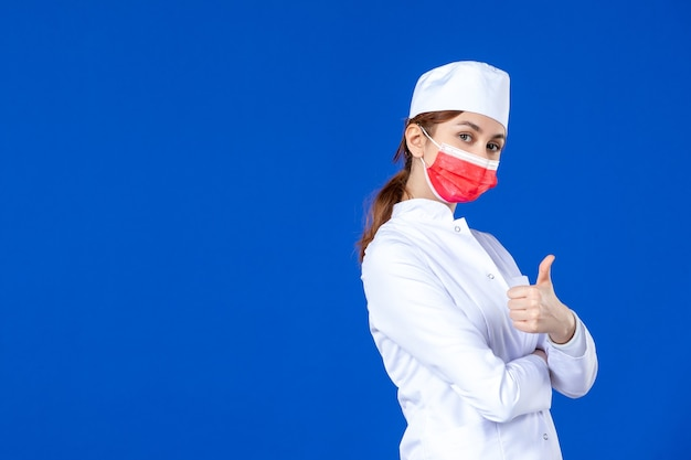 Junge krankenschwester der vorderansicht im medizinischen anzug mit roter maske auf blauer wand