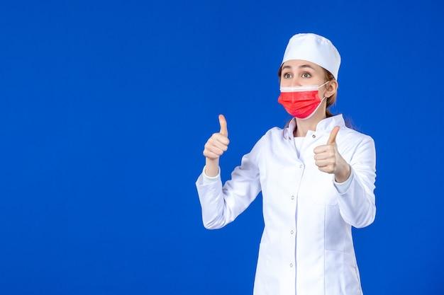 Junge krankenschwester der vorderansicht im medizinischen anzug mit roter schutzmaske auf blauer wand