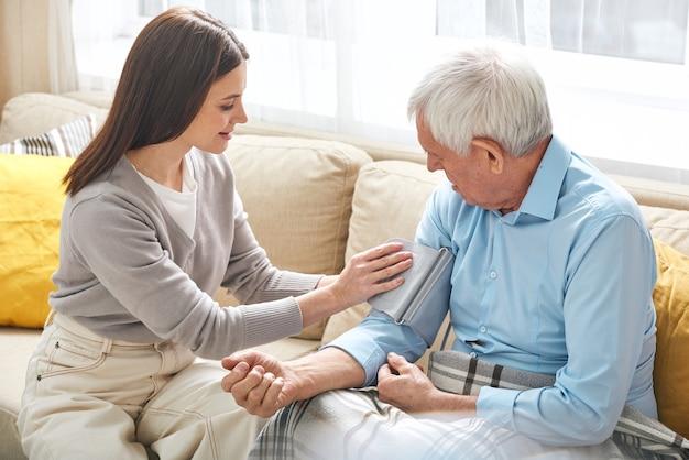 Junge krankenschwester, die auf sofa sitzt und druck des älteren mannes im wohnzimmer nimmt, sie besucht patient zu hause