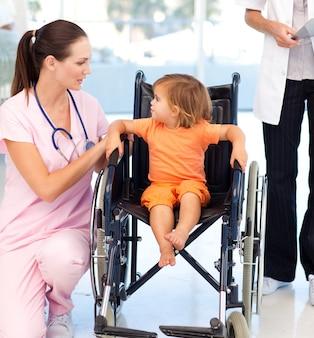 Junge krankenschwester, die mit einem baby in einem rollstuhl spricht