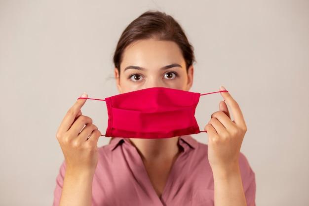 Junge krankenschwester hält eine rote gesichtsmaske vor sich und bereitet sich darauf vor, sie aufzusetzen.
