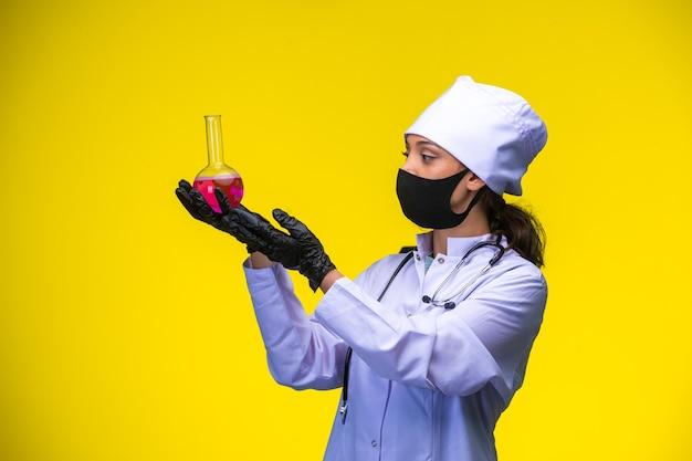 Junge krankenschwester in gesicht und handmaske hält chemiekolben mit beiden händen