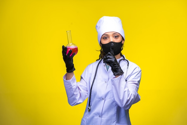 Junge krankenschwester in gesichts- und handmaske hält eine testflasche auf gelb.