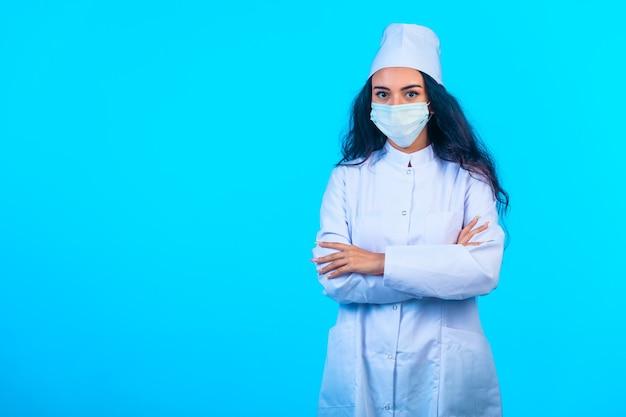 Junge krankenschwester in isolierter uniform, die schließende hände hält und selbstbewusst aussieht