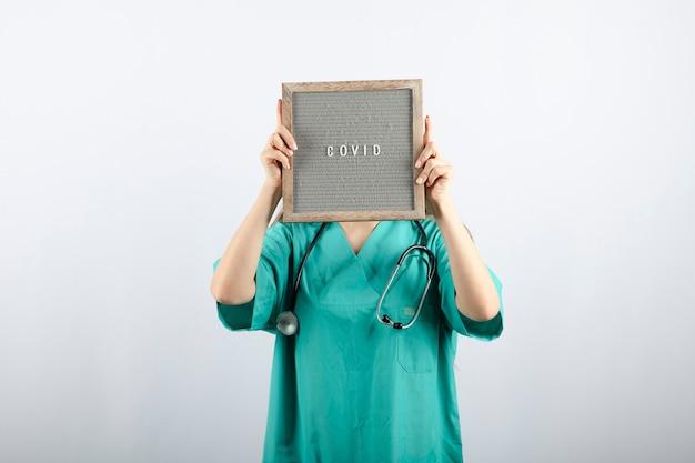 Junge krankenschwester in medizinischer maske mit stethoskop, das das gesicht mit einem rahmen bedeckt
