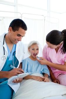 Junge krankenschwester, welche die temperatur ihres kinderpatienten nimmt
