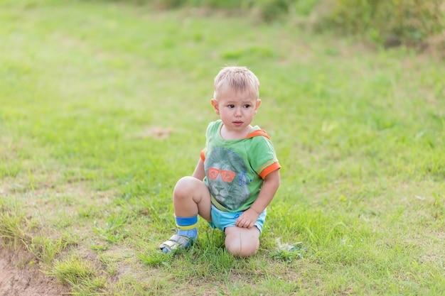 Junge kratzt sich am bein von einem mückenstich, während er auf einem grünen rasen steht. ein insektenstich.